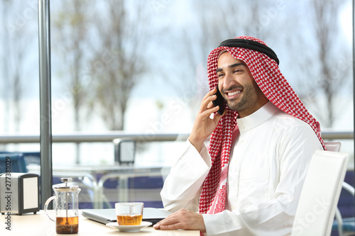 Fotografija Happy arab man talking on phone in a coffee shop