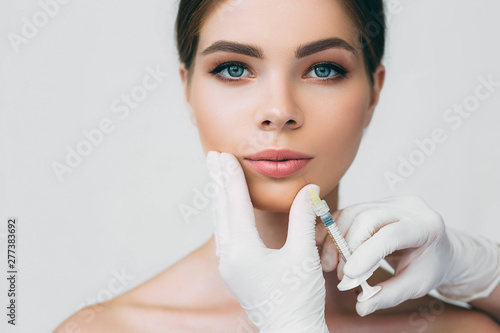 beautiful woman getting injection in her mouth for lip augmentation Poster Mural XXL