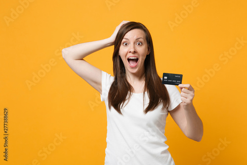 Fototapeta Portrait of surprised young woman in casual clothes keeping mouth open, putting hand on head, hold credit bank card isolated on yellow orange background. People lifestyle concept. Mock up copy space. obraz na płótnie