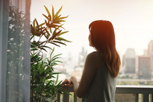 Young Asian Woman Feeling Lonely While Looking Out To The City View From Room Balcony