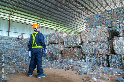 Pinturas sobre lienzo  workers in landfill dumping, Garbage engineer, recycling, wearing a safety suit standing in the recycling center have a plastic bottle for recycling in the factory