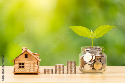 Fotografía  Coin jar and stack, and model house on wooden desk on green tree background, mor