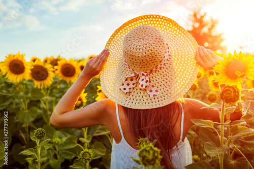 Young woman walking in blooming sunflower field holding straw hat. Summer vacation