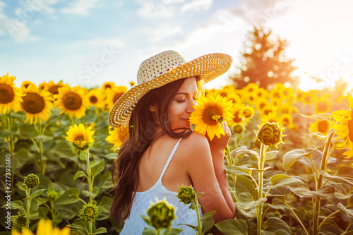 Tuinposter Zonnebloem Young woman walking in blooming sunflower field and smelling flowers. Summer vacation
