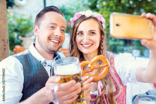Fotografia, Obraz  Paar im Biergarten in Bayern macht ein Selfie mit dem Telefon