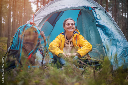Foto auf Leinwand Cappuccino young beautiful woman with a tent in the forest, camping, solo travel, nature concept