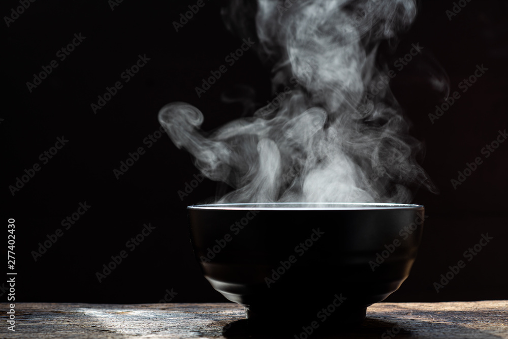 Fototapety, obrazy: Bowl of hot soup. steam of hot soup with smoke wood bowl on dark background.selective focus,hot food concept