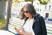 Outdoor Picture Of Busy Modern Middle Aged Woman In Stylish Black Sunglasses And Leather Jacket Messaging Online Using Smart Phone, Sitting On Empty Street In The Morning. Technology And Communication