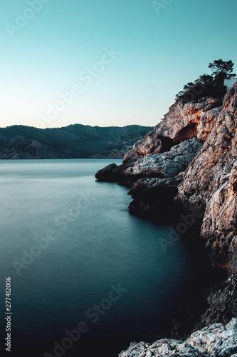 Motiv-Rollo Basic - Long exposure shot with blurry soft ocean water and the rock stone coastline on a vacation summer day. Port d' Andratx, Port Andratx, Mallorca Spain Balearics