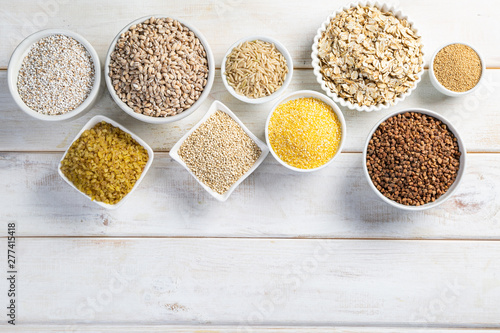 Fototapeta Selection of whole grains in white bowls - rice, oats, buckwheat, bulgur, porridge, barley, quinoa, amaranth, on white wood background obraz