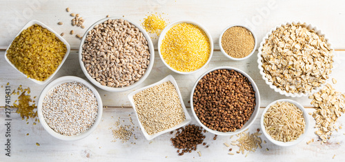 Photographie Selection of whole grains in white bowls - rice, oats, buckwheat, bulgur, porrid