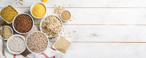 Tableau sur Toile Selection of whole grains in white bowls - rice, oats, buckwheat, bulgur, porrid