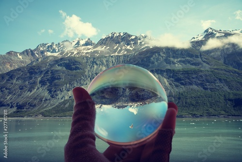 Snow capped mountains in Glacier Bay National Park and Preserve, reflected in crystal ball held by hand.