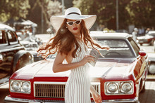 Street Fashion Portrait Of Young Elegant Luxury Lady Wearing White Sunglasses, Wide Brim Hat, Striped Linen Jumpsuit, Holding Animal Print Zebra Purse, Posing Near Red Car. Copy, Empty Space For Text