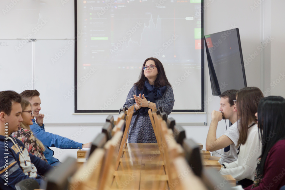 Fototapety, obrazy: Female professor explain lesson to students and interact with them in the classroom.Helping a students during class. University student being helped by female lecturer during class.