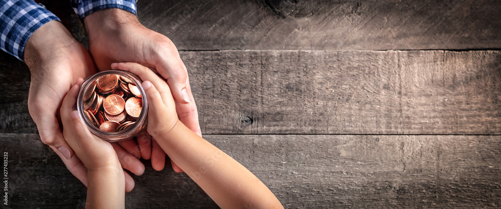 Fototapety, obrazy: Hands Of Father Giving Jar Of Coins To Child On Wooden Table Background - Inheritance / Parent Providing For Children Concept
