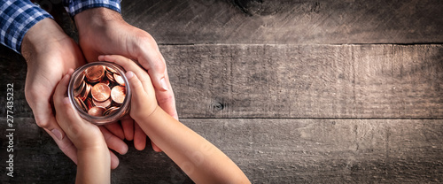 Fotografía Hands Of Father Giving Jar Of Coins To Child On Wooden Table Background - Inheri