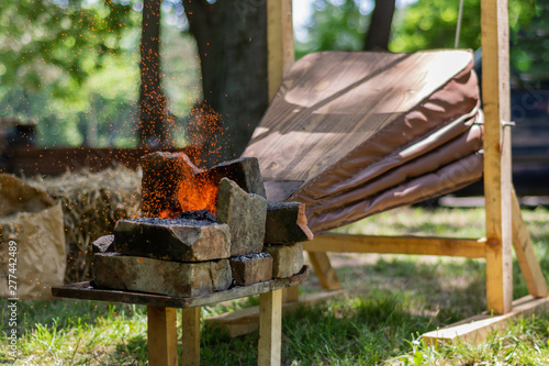 Medieval bellows make the fire of coals and sparks fly from outdoor blacksmith tool Canvas Print