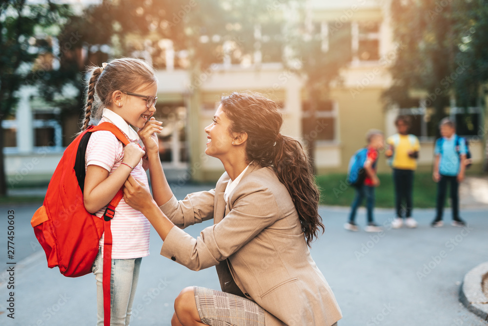 Fototapety, obrazy: First day at school. Mother leads a little child school girl in first grade.