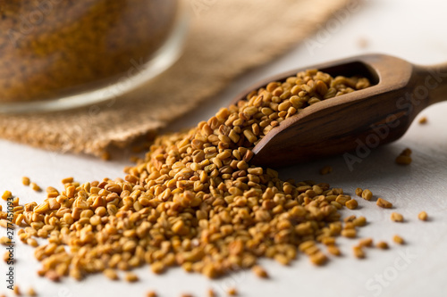 Fototapeta Dried, raw fenugreek seed in wooden scoop with storage glass jar on white wooden table background obraz