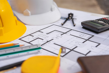 Architect desk with blueprint and hard hat constuction building.