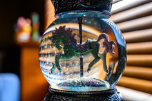 Glitter Snow Globe With Carousel Horse.  Window Blinds In Background