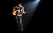 Guitarist, Music. A Young Man Plays An Acoustic Guitar On A Black Isolated Background