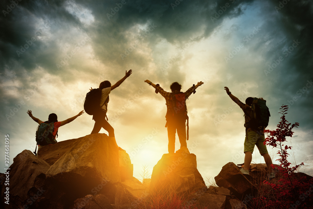 Fototapety, obrazy: Celebrating life of Hikers climbing up mountain cliff. Climbing group helping each other while climbing up in sunset. Concept of help and teamwork, Limits of life and Hiking success full.