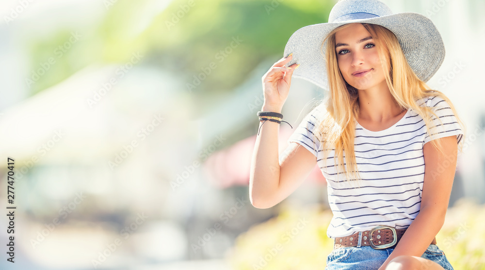 Fototapety, obrazy: Summer portrait of young beautiful woman in hat sitting on bench in park