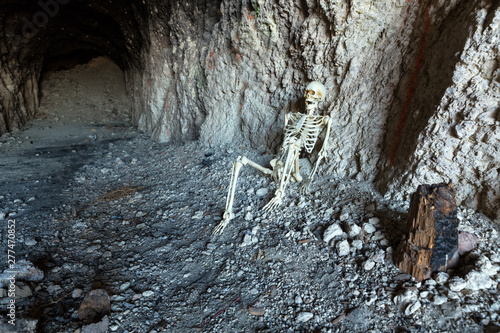 Skeleton in a dark cave in the ground lying on rocks
