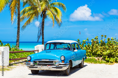 Fotobehang Cubaanse oldtimers Amerikanischer blau weisser Oldtimer parkt parkt direkt am Strand unter Palmen in Varadero Kuba - Serie Kuba Reportage