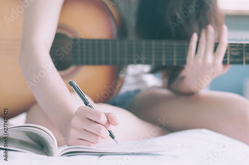 Fototapeta Young beautiful woman sitting on her bed in the bedroom holding guitar composing
