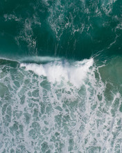 Aerial View Of A Waves Crashing And Rolling In The Ocean.