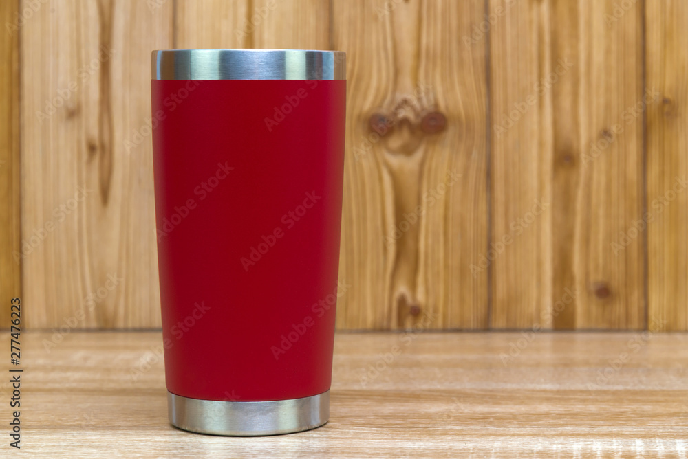 Fototapeta Red colour stainless steel tumbler or cold and hot storage cup on wood.