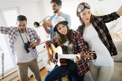 Group of friends playing guitar and partying at home - 277488224