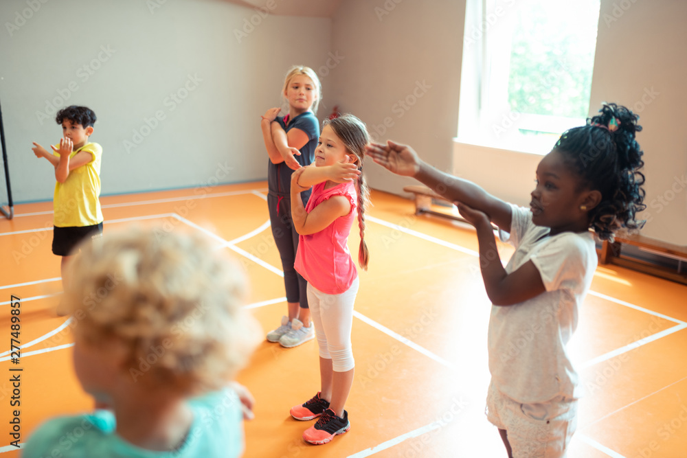 Fototapety, obrazy: Elementary school children working out at sports lesson.