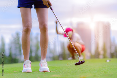 Fotomural  young woman golf player success to putting golf ball into the hole on the green