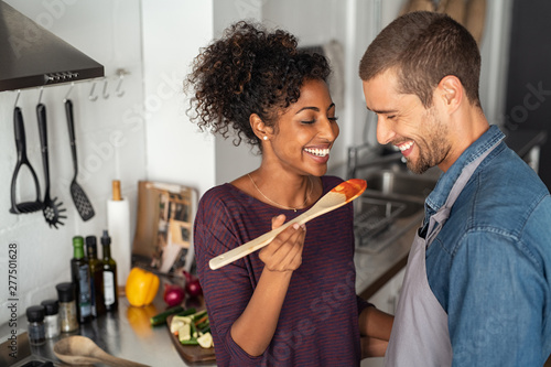 Papel de parede Multiethnic couple tasting food from wooden spoon