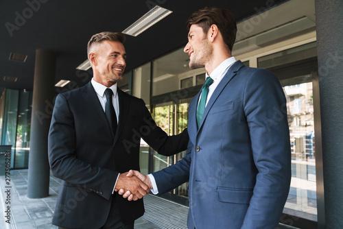 Canvas-taulu Portrait closeup of two successful businessmen partners shaking hands outside jo