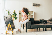 Smiling African American Woman Sitting Opposite Electric Blowing Fan At Home