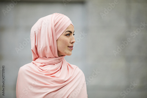 Poster Personal Side view of content introspective young Muslim woman of Islamic faith wearing pink hijab looking into distance outdoors