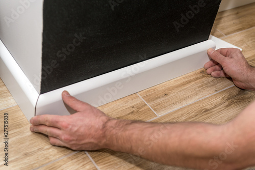 Close up of mans hands installing skirting board Wallpaper Mural
