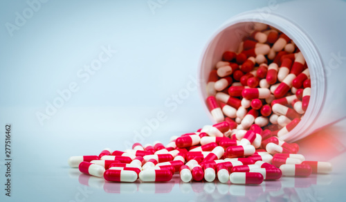 Photo  Red and white capsules pill spilled out from white plastic bottle container