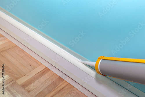 Mans hand caulk skirting board with caulking gun and silicone cartrige Fototapete