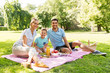 canvas print picture - family, leisure and people concept - happy mother, father and little son having picnic at summer park