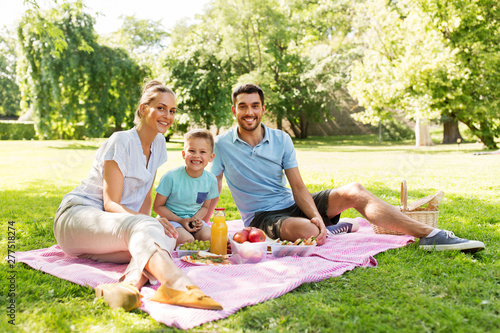 Poster Personal family, leisure and people concept - happy mother, father and little son having picnic at summer park