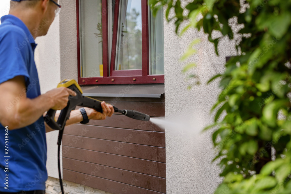 Fototapeta house facade cleaning service. man washing wall with high pressure washer