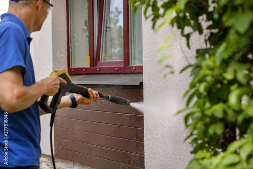 Fototapeta house facade cleaning service. man washing wall with high pressure washer obraz
