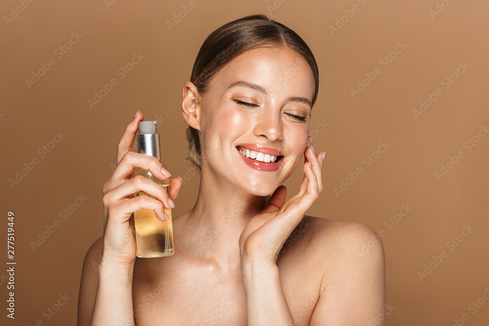 Fototapety, obrazy: Image of adorable half-naked woman smiling at camera and holding face oil