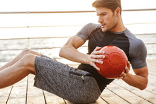 Photo Of Concentrated Man In Tracksuit Doing Exercise With Red Fitness Ball While Working Out On Wooden Pier At Seaside